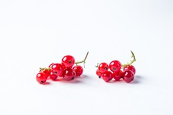 Red currants on a white background. Two brushes of red currant lie next to each other