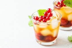 Red currants, summer berry iced tea in glasses. Space fot text.