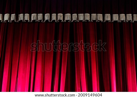 Red curtain on the theater stage, illuminated by spotlights. Intermission between performances. The concept of the theater. Stock photo ©