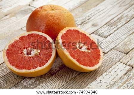 red cut grapefruit on white grunge wood table with paint peeling off