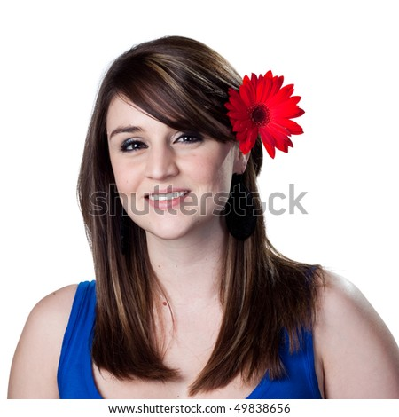 Red daisy in the hair of a beatiful young woman