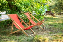 Red Deckchairs in autumn garden. Two deckchairs on summer green lawn. Lounge sunbed. Wooden garden furniture on grass lawn outdoor for relax. Backyard exterior. Garden landscape with chairs in nature.