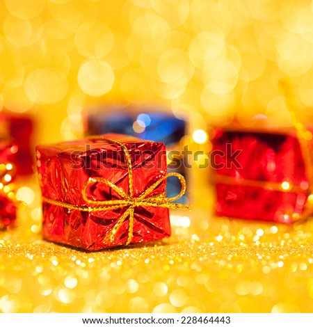 Red decorative box with holiday gift on gold glitters background