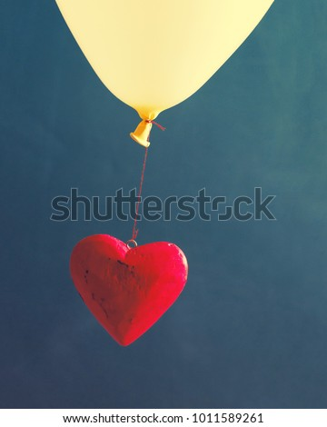 Red decorative heart on a balloon against a dark background. Romantic image by St. Valentine's Day #1011589261