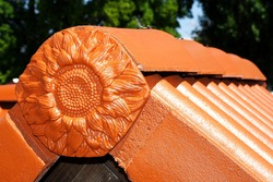 Red decorative sunflower on a concrete roof, decorative finis