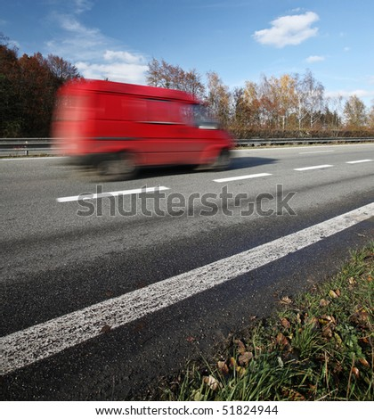 Red delivery/cargo van going fast on a highway