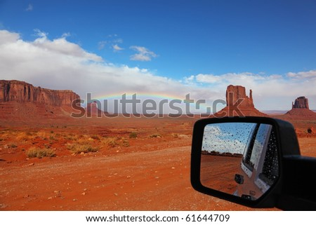 Red Desert after rain and a rainbow on it reflected in the car mirror