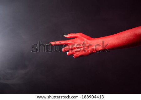 Red devil pointing hand with black sharp nails, extreme body-art, Halloween theme