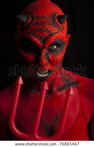 Red devil woman with her trident. Low key lighting.