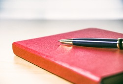 Red diary and pen on white background