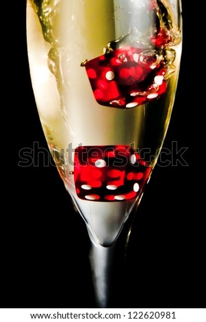 red dice dropping in the champagne flute on black background