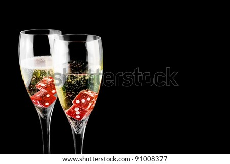 red dice in a champagne flute on black background
