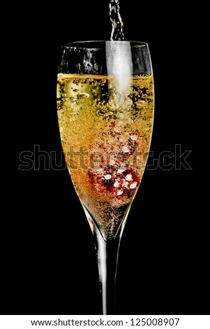 red dice in the glass of champagne being filled with a lot of bubbles on black background