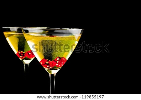 red dice in two cocktail glasses with gold bubbles on black background with space for text