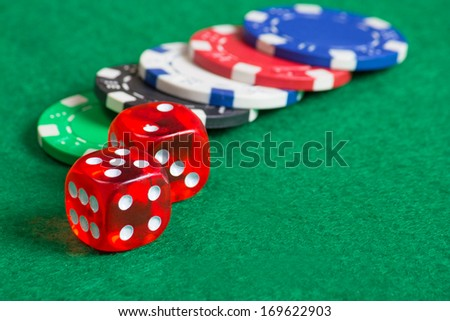 red dice on a casino table with colorful chips
