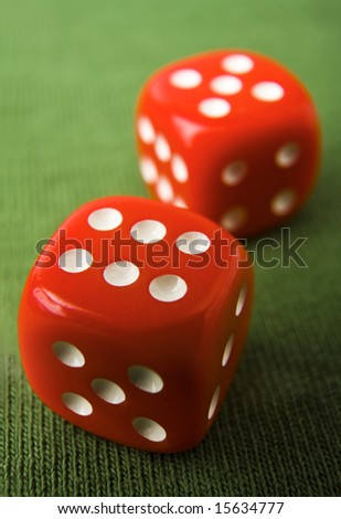 Red dice showing 6 and 5 on green felt