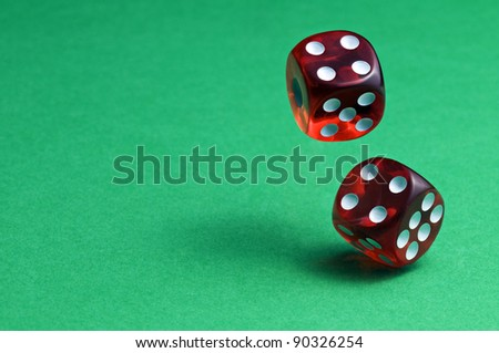Red dices in midair on green background close up