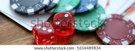 Red dices lying with casino chips as gambling symbol close-up