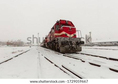 Red diesel train (Orient Express) is moving in the snow-covered railway platform from the capital city of Turkey; Ankara to Kars eveyday. It is very popular on winter holidays.  Stok fotoğraf ©