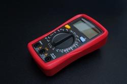 Red digital multimeter on black background - Multimeter is an electronic measuring instrument for voltage, amper, resistance