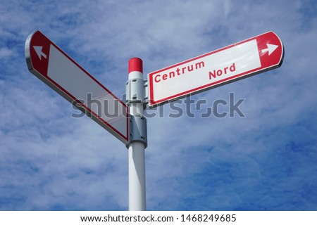 red direction sign on the pole against the blue cloudy sky. white arrow signal against heaven with clods. Nord Centrum. empty frame #1468249685