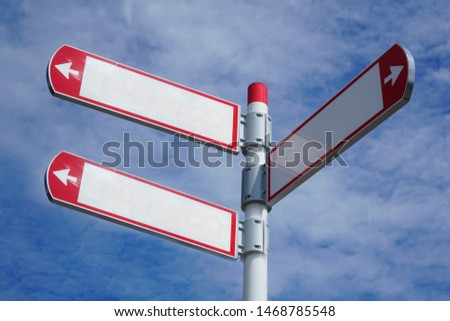 red direction sign on the pole against the blue cloudy sky. white arrow signal against heaven with clods.  empty frame blank  #1468785548
