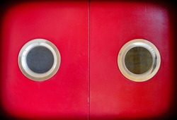 Red door with two round windows, a graphic element resembling a toy robot head.