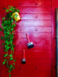 Red door wooden paint by oil color have  decorate brush paint and plastic flower yellow pot with  lock key on the entrance, white walls, antique architectural elements,selective focus.HDR grain tone.