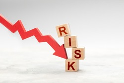 Red down arrow knocks down the cube RISK. Risky fall or investment concept.