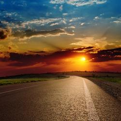 red dramatic sunset over asphalt road