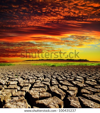 red dramatic sunset over dry cracked earth