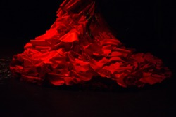 Red dress with ruffles and frills used to wear as a costume for performing flamenco dancing, on a black background