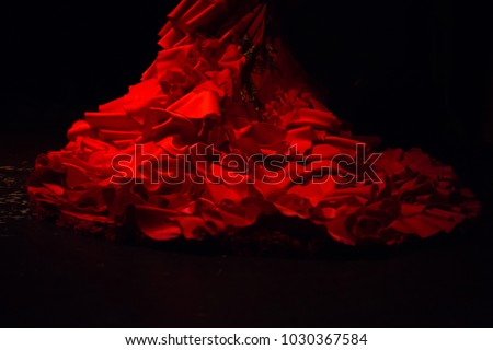 Photo of  Red dress with ruffles and frills used to wear as a costume for performing flamenco dancing, on a black background