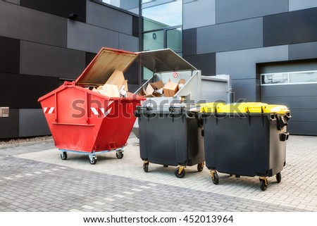 Red dumpster, recycle, waste and garbage bins near new office building. Backyard view