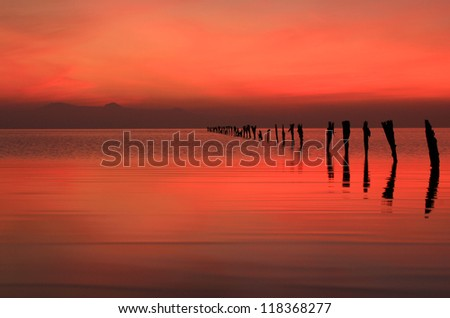 Red dusk sky with old fence posts at the Great Salt Lake, Utah, USA.