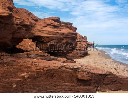 Red earth cliffs and arches along the eroding shoreline of Prince Edward Island, Canada