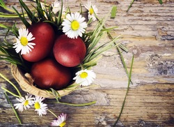 Red easter eggs in basket with flowers