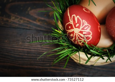 Red easter eggs in wooden basket with grass