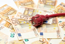 Red electric cable with plug on euro banknotes. Cost of electricity and expensive energy concepts.