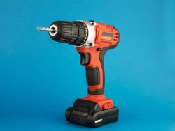 red electric drill with a nozzle on a blue background