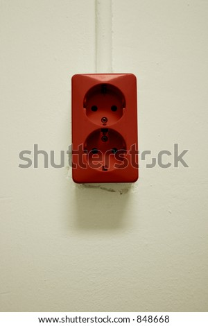 red electrical plug socket on a white wall