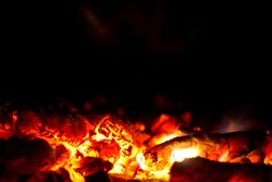 Red ember on black background. Hot red embers background.