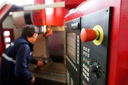red emergency button focused on the keypad of a CNC milling machine, while the operator is clamping a vise