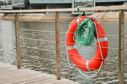 Red emergency lifebuoy with green rope on pier of the city park. Closeup of lifebuoy on dock. Rescue equipment for emergency on water.