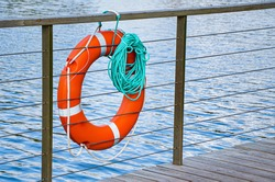 Red emergency lifebuoy with turquoise rope on pier near sea. Closeup of lifebuoy on dock. Rescue equipment for emergency on water.
