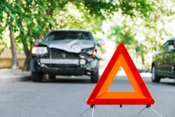 Red emergency stop triangle sign on road during a car accident. Broken gray car in road traffic accident. Car crash traffic accident on city road after collision