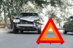 Red emergency stop triangle sign on road in car accident scene. Broken SUV car on road at traffic accident. Car crash traffic accident on city road after collision