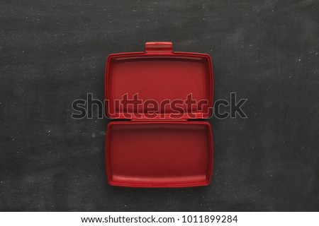 Red empty open plastic lunch box for food storage on black background with copy space, top view