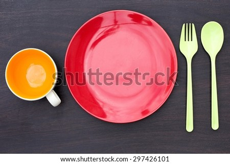 Red empty plate, spoon and fork green plastic. Orange empty coffee cup and placed on a wooden table.