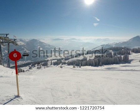 Red empty ski slope on a cold winter day in Ski Resort Wilder Kaiser - Brixental (Austria, Tirol). Beautiful sight over the mountains in Tirol on a sunny day.